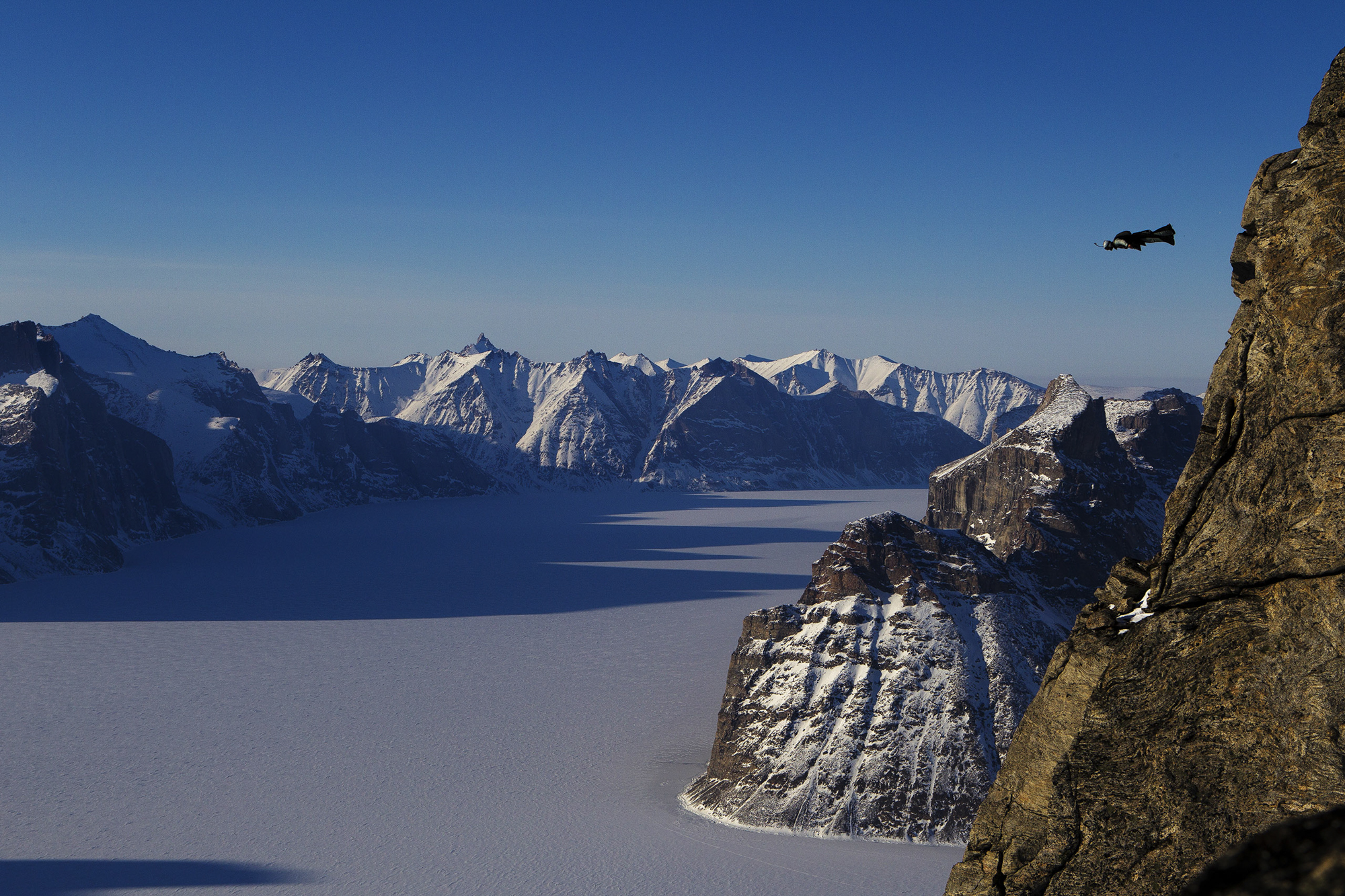 Overlooking Sam Ford Fjord, Jim Mitchell leaps from Ottawa Peak in his wingsuit on Baffin Island/Photo by Krystle Wright